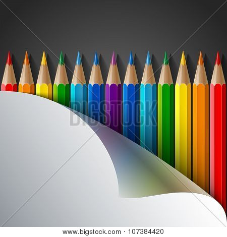 Rainbow colored pencils and realistic white paper turn corner on dark grey background