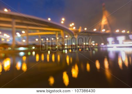 Reflection of blurred suspension bridge and highway intersection at night