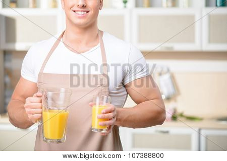 Young male kitchen worker holding a glass of juice.