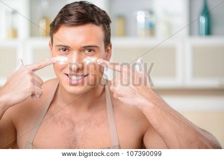Young smiling man puts some flour on his face.