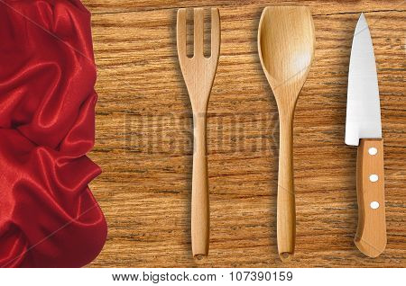 Wooden Spoon, Fork And Knife On Cutting Board With Red Cloth