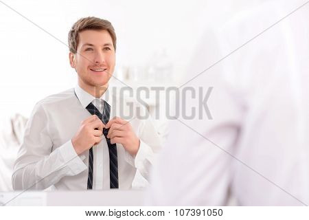 Handsome guy fixes up his tie.