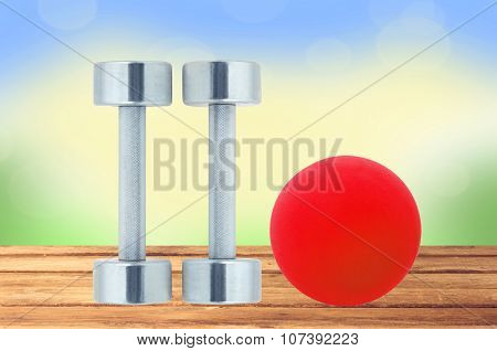 Chromed Fitness Dumbbells And Red Ball On Wooden Table Over Nature Background
