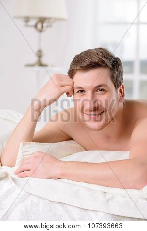 Young man in bed rests against a pillow.