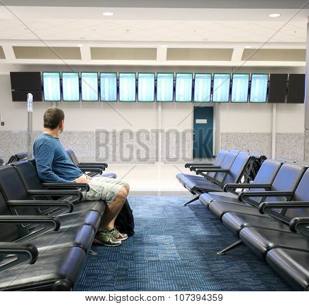 Man is looking at a flight screen in an airport.