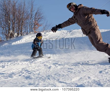 Man Snowboarder And Little Skier