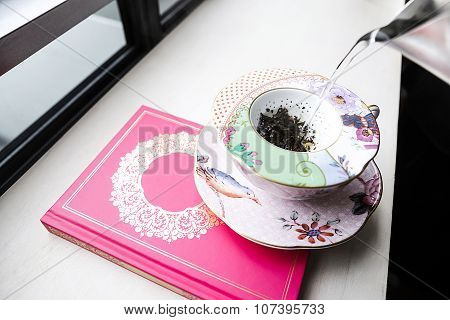 Porcelain Tea Cup On Top Of A Book
