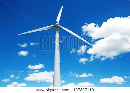 Wind Generator Turbine Against Deep Blue Sky With Clouds