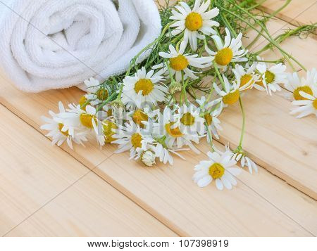 White Towel And Camomile Bouquet On The Natural Wood Planks