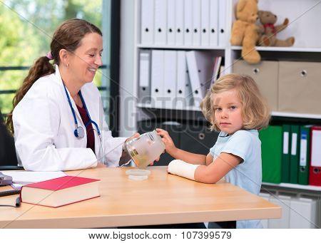 Female Pediatrician Bandaging The Arm Of A Little Girl