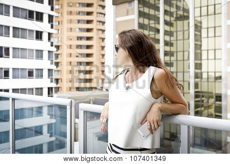 Brunette Standing In The Courtyard Of A Condominium