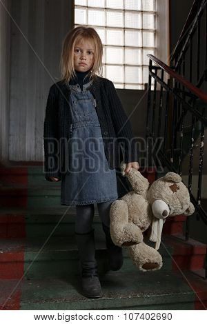 Miserable girl standing on the staircase