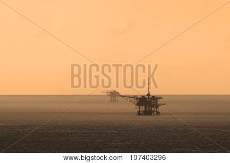 Offshore Platform In The Middle Of The Ocean With Beautiful Sunset
