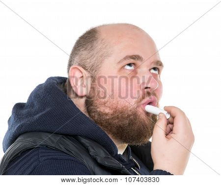 Bald Bearded Fat Man Uses A Protective Lipstick