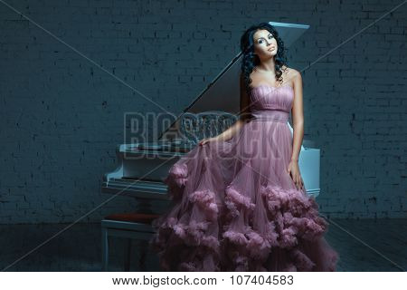 Beautiful Woman Posing Next To A White Piano.