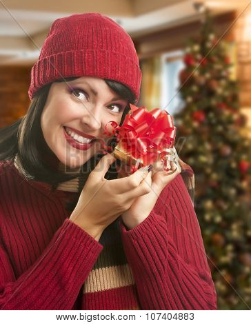 Happy Woman Holding Wrapped Gift in Christmas Setting.