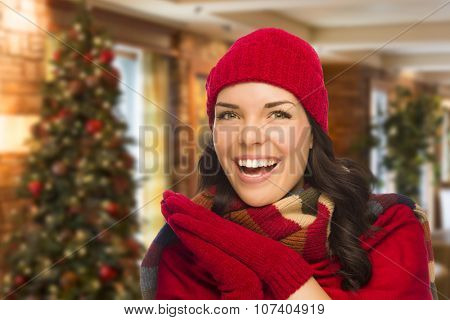 Happy Mixed Race Woman Wearing Mittens and Hat In Christmas Setting.