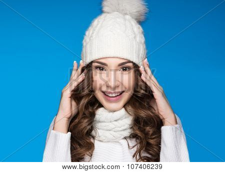 Beautiful girl with gentle makeup, design manicure and smile in white knit hat. Warm winter image. B
