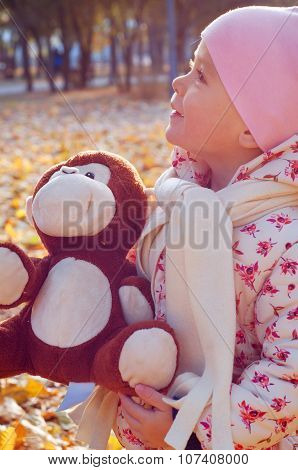 Cute Little Girl Playing In The Leaves With Her Monkey Toy