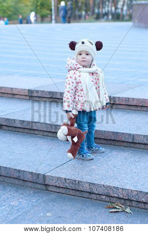Cute Little Girl In A Funny Panda Hat Standing Alone With Her Toy