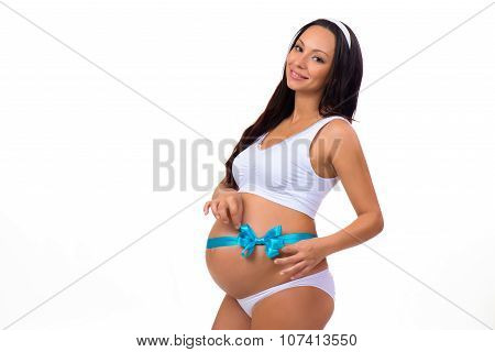 Happy Pregnancy. Smiling Pregnant Woman Tying A Blue Ribbon Bow On Her Belly