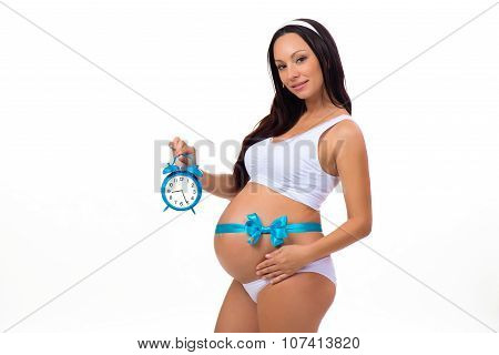 9 Months. Happy Pregnancy. Pregnant Woman With Alarm Clock In His Hands And Blue Bow On The Tummy