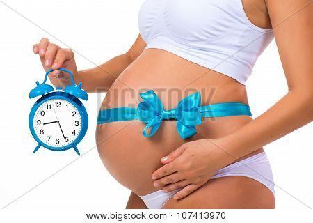 Close-up Of A Pregnant Belly With A Blue Ribbon And An Alarm Clock. Concept Of Pregnancy