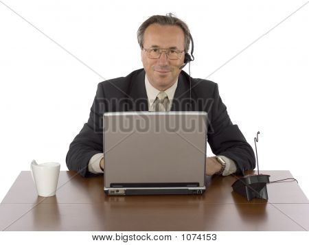 Businessman At The Desk With Headset