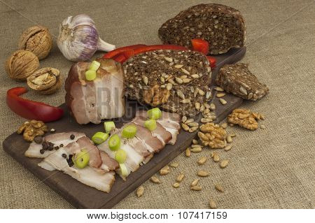Preparing home-made snacks for the guests. Cutting board with smoked bacon and bread