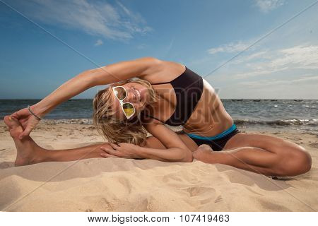 Young woman extends her back while and doing yoga on beach with the ocean in the background.