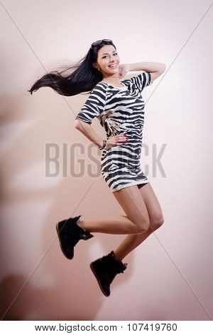 young woman jumping joyfully in zebra dress and snickers