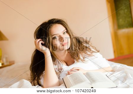 Young lady in white shirt lying on bed reading book