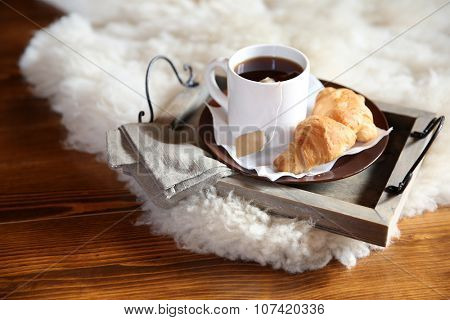 Wooden tray with light breakfast on white rug
