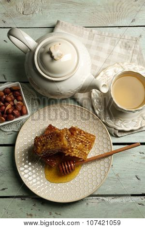 Honeycomb, bowl with honey, teapot and nuts on color wooden background