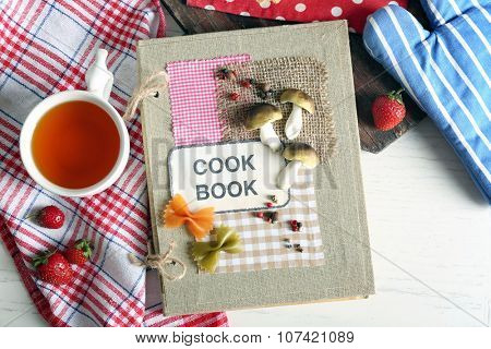 Decorated cookbook with cup of tea and tasty cake on the table