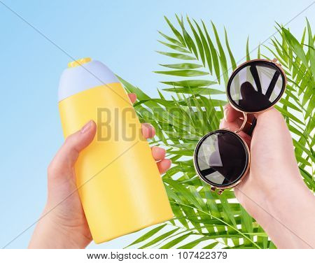 Bottle of suntan cream and sunglasses in hand on palm leaves background