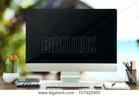 Computer on wooden table on nature background