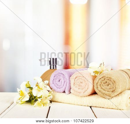 Soft towels with dispenser and flowers in bathroom
