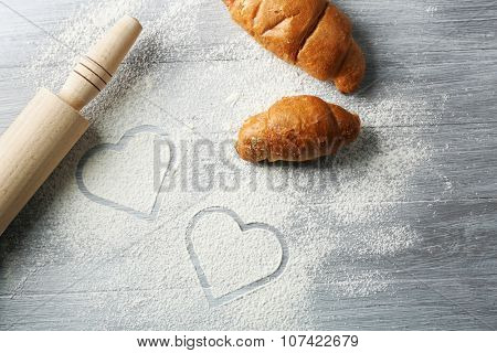 Hearts of flour and rolling pin on light background