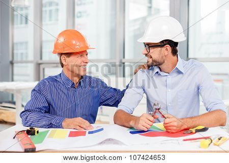 Cheerful male engineers are discussing the construction