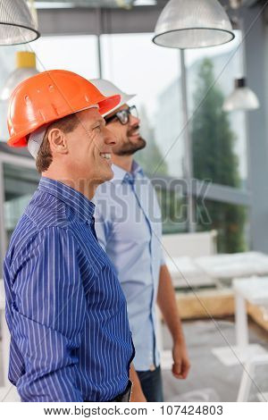 Cheerful two male engineers are working with joy
