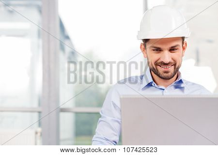 Attractive young architect is working with the laptop