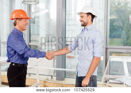 Cheerful male engineers made the deal with handshake