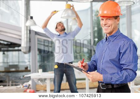 Cheerful two male workers with colored helmets