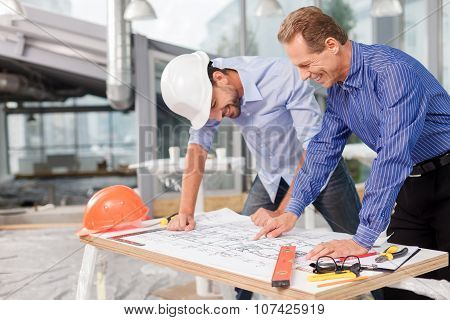 Cheerful male architects are discussing the project