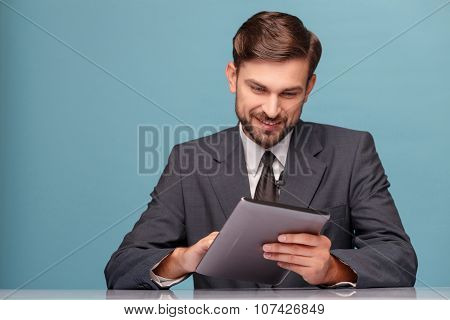 Handsome newscaster working at studio with laptop
