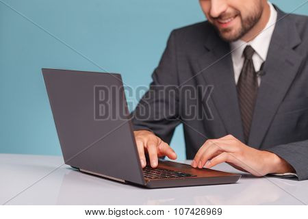 Cheerful male anchorman is working with a notebook