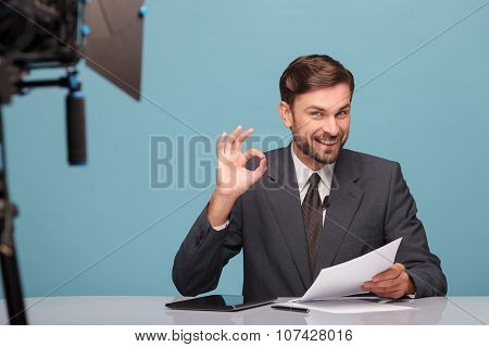 Attractive young tv newscaster is gesturing positively