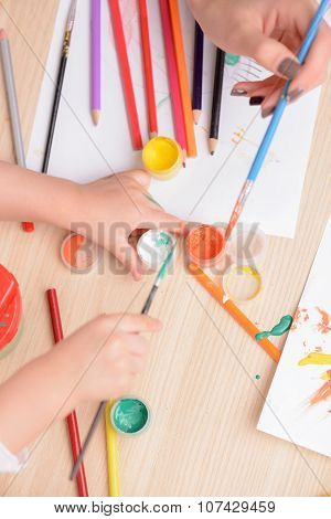 Cheerful woman and her child are drawing