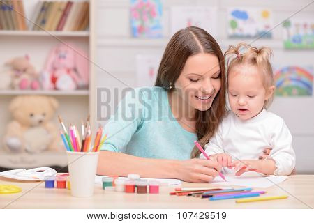 Beautiful friendly family is painting with joy